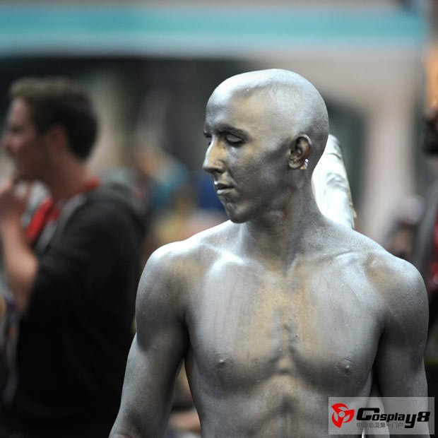 A man dressed as the Silver Surfer walks through the exhibition